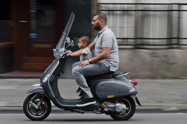 man and child riding scooter